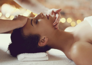 therapist massaging woman's face